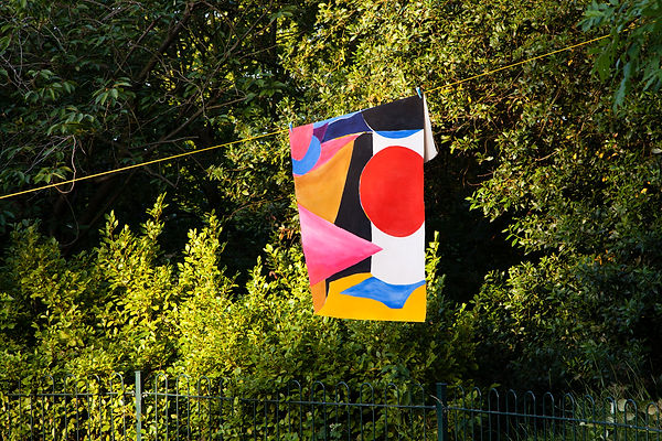 Draped abstract colourful painting, hanging on a line outdoors, photographed in the afternoon light.