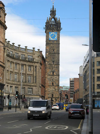 Tolbooth Steeple at Glasgow Cross. A tallk sone clock tower with blue and gold face. A crescent of sandstone buildings can be seen on the left, vehicles in the foreground and modern buildings frame the right hand side.