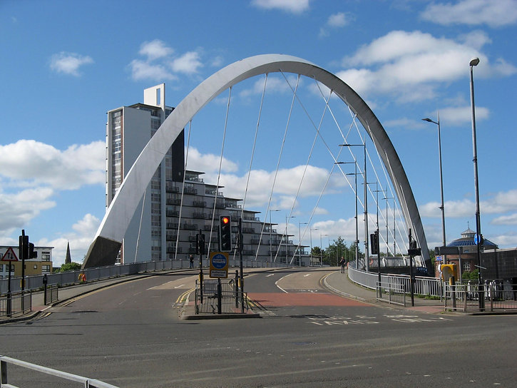 The Squinty Bridge. Photo of the arc-shaped road bridge over the River Clyde. The metal supports are gleaming in the sun, and a stepped block of flats can be seen in the background.