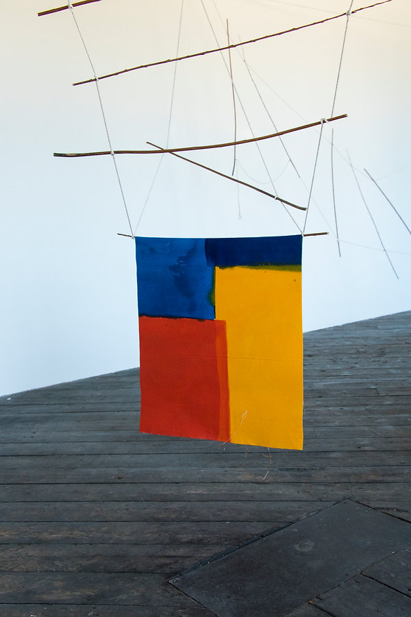 Blue, Red and Yellow abstract painting draped from a sculptural structure of sticks and strings.