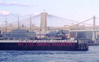 "Lawrence Weiner's conceptual artwork ""At the Same Moment"" painted on pilings in the East River, as seen from the Staten island Ferry. Behind can be seen the Brooklyn Bridge and the Manhattan Bridge."