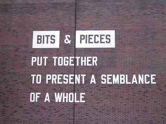 Photograph of artwork by Lawrence Weiner called  Bits & Pieces Put Together to Present a Semblance of a Whole made of laser-cut aluminum typography on brick. Walker Art Center, Minneapolis, Minnesota.