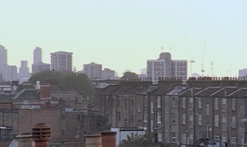 Charlotte Ginsborg , Rose Kowalski, Wake Work, (film still)  2007. Courtesy of the artists and LUX, London. A colour film still depicting a city scene with tall terraced housing, blocks of flats and taller buildings in the distance. The colour is slightly washed out.