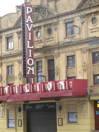 The Pavilion Theatre. A sandstone building with dark red and white signage: the name PAVILION hangs vertically above the entrance.