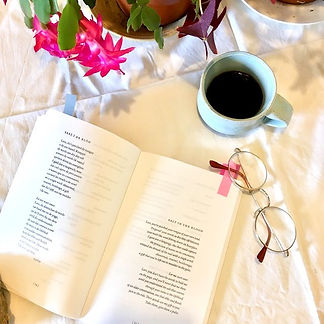 A photo of an open book, cup of black coffee and round spectacles seen from above.