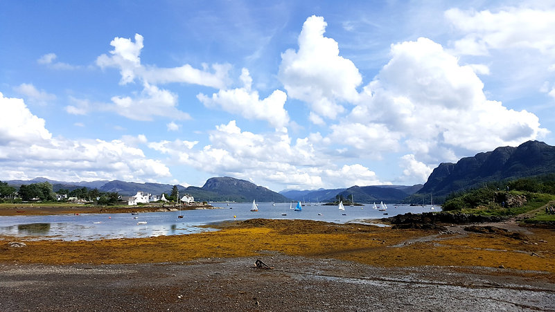 Scottish harbour scene with white and blue sailing boats, small white cottages and mountains in the distant. Rust coloured ground with blue loch and blue and white cloudy sky.