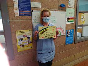 Nurse with rainbow sign.