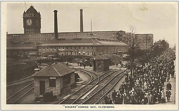Workers leaving the Singer Sewing Machine Factory. Public domain image. The image is an aged black and white postcard depicting the Singer factory, with clock tower and two tall chimneys, railway lines running towards it and crowds of workers walking away from the factory, facing towards the camera.