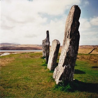 Standing stones on a flat area of grass with a coastal area in the distance.