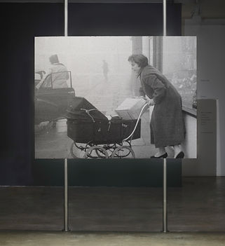Kate Davis, 'Weight', installation view 'Nudes Never Wear Glasses'. Photograph of video projection depicting a woman pushing a buggy, it looks like a 1950s scene.