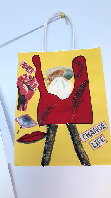 Artwork made by WASLER ART participant paper bag that has been decorated on the outside in bright yellow with various images and text collaged onto it. There is a red figure and a red fist, a crying eye and stitched together lips, the text reads Power and Change Life.