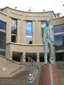 Photograph of the exterior of the Glasgow Concert Hall, with the Donald Dewar statue in the foreground.