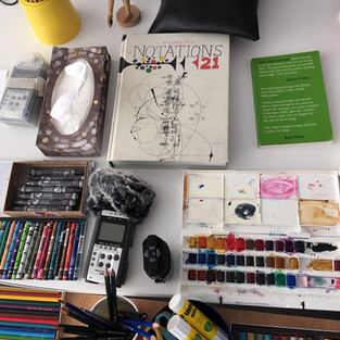 Sound Workshop Documentation. Looking at Graphic Scores and Notations.  Image description: Art materials laid out on table with Zoom Recorders and two books.