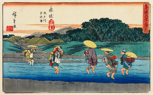 Fujieda by Ando Hiroshige (1797-1858), an illustration of travelers crossing a stream by carrying a person or a bundle on their backs in a rural area with mountains and a village in the background.