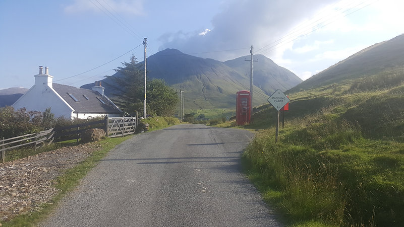 Scottish country road with small white cottage on the left, a red phone box on the right and mountains in the distance.