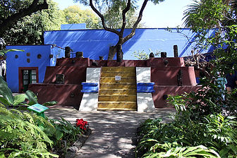 A colour photograph of a garden, yellow painted stairs with chocolate brown stepped walls and bright blue pots leading to a bright blue painted low-rise building. The building is Frida Kahlo's Casa Azul, or Blue House. The sun is shining.