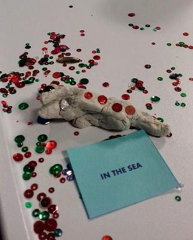 Resident in Ward 52, QEUH, untitled sculpture  2021, mixed media. Clay sculpture lying within a mix of sequins and a small blue square of paper with In the Sea written on it.