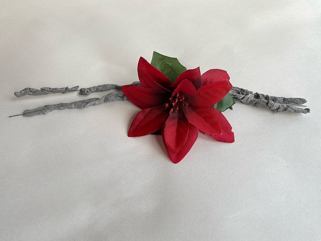 Jean Proctor at Greenfield Park Care Home, untitled sculpture, 2021, mixed media. Red fabric flower attached to wire and clay stems.