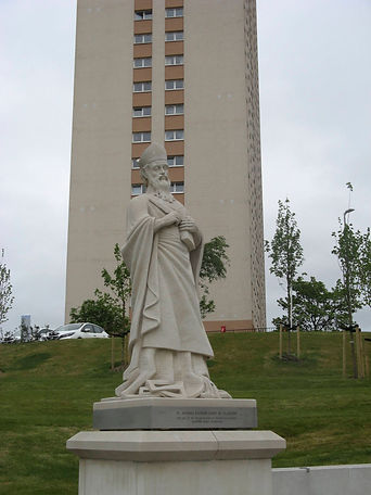 White Saint Mungo statue with block of flats in the background.