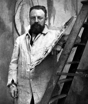 A black and white photo of Matisse, leaning against a ladder and holding a messy paint palette. He has a beard and round glasses and is wearing a white painter's jacket.