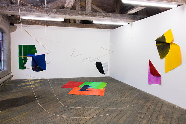Installation view of abstract paintings that hang from the wall, from lines in the exhibition space and are laid flat on the floor.
