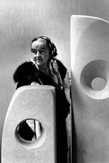 A black and white photograph of Barbara Hepworth standing with two of her sculptures.