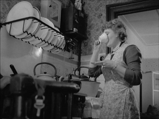 Film still: Kate Davis,  Weight, UK, 2014, HD Cam, B&W/ Colour, Stereo, 11:06 min. Courtesy of the artist.  A black and white film still of a white woman standing next to the stove and sink  of a 1940s/1950s kitchen, she is drinking from a china cup , and is wearing a flowery apron.