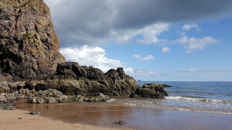 Rocky sandy beach scene with cloudy blue white and grey sky.