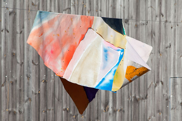 Abstract colour painting on fabric draped over a line hanging in front of gey panelling.