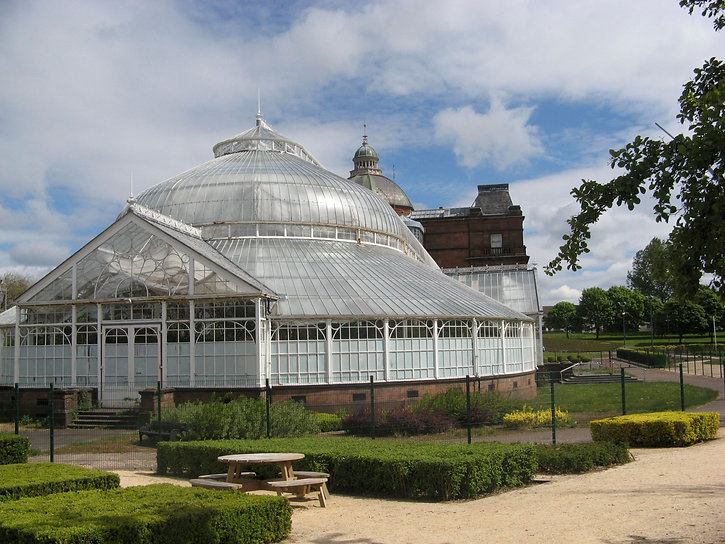 The People's Palace and Winter Gardens. A large glasshouse with neat hedges in the foreground.
