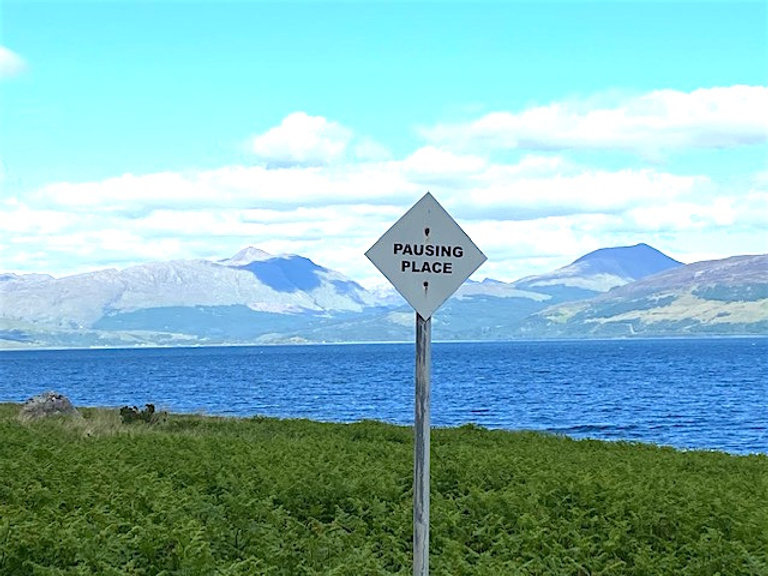 Thomas A Clark, Pausing Place. Photograph of a mountainous landscape in the distance, a body of water, grass in the foreground, and a roadsign (which is the artwork) that reads: PAUSING PLACE.