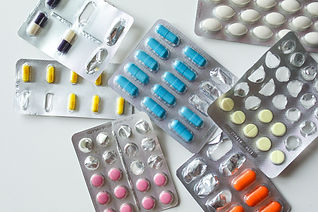 Different coloured tablets in blister packs.