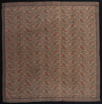 Wool & silk Paisley shawl, circa 1830. Public domain image. A photograph of a piece of fabric made from a Paisley design; a repeated pattern of a teardrop type shape in muted brown and cream colours.