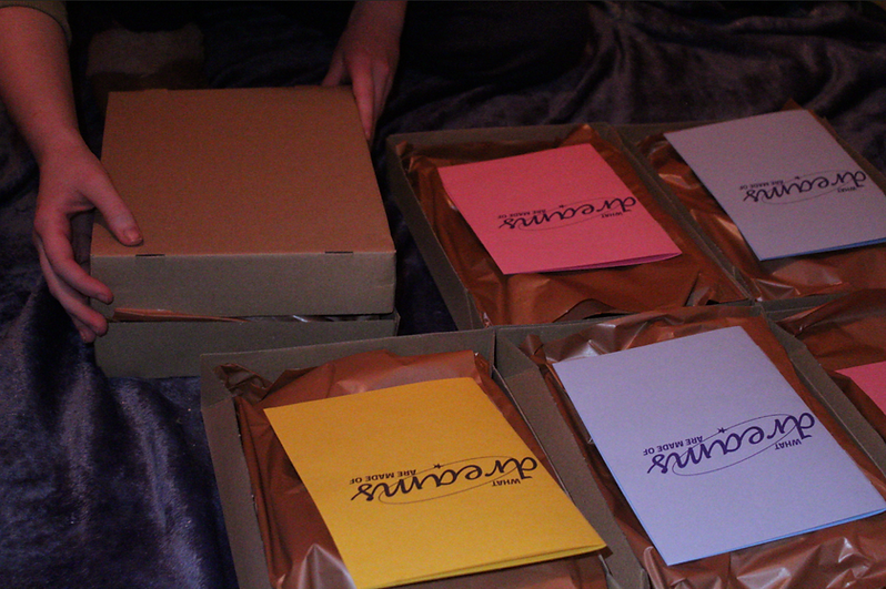 'What Dreams are Made of' sculpture boxes, being prepared for the art sessions. Boxes are open with booklets visible inside.