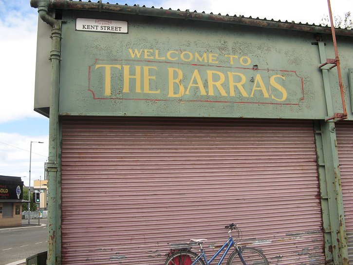 The Barras market: a slightly faded green market shopfront, with yellow letters reading WELCOME TO THE BARRAS, a faded red shutter and blue bike can also be seen.