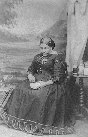 Photograph of Mary Seacole, c. 1873. Black and white photo of woman in a grand dress looking downwards.