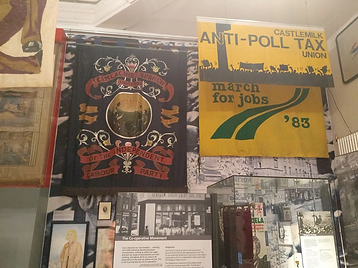 Image: Inside The People's Palace. Courtesy of Hailey Maxwell. In shot is a yellow Castlemilk Anti-Poll Tax banner from 1983 and a banner for the Camlachie Branch Independent Labour Party.