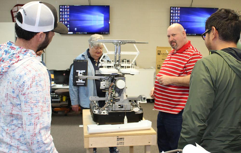 Team servicing muti-needle sewing machine.