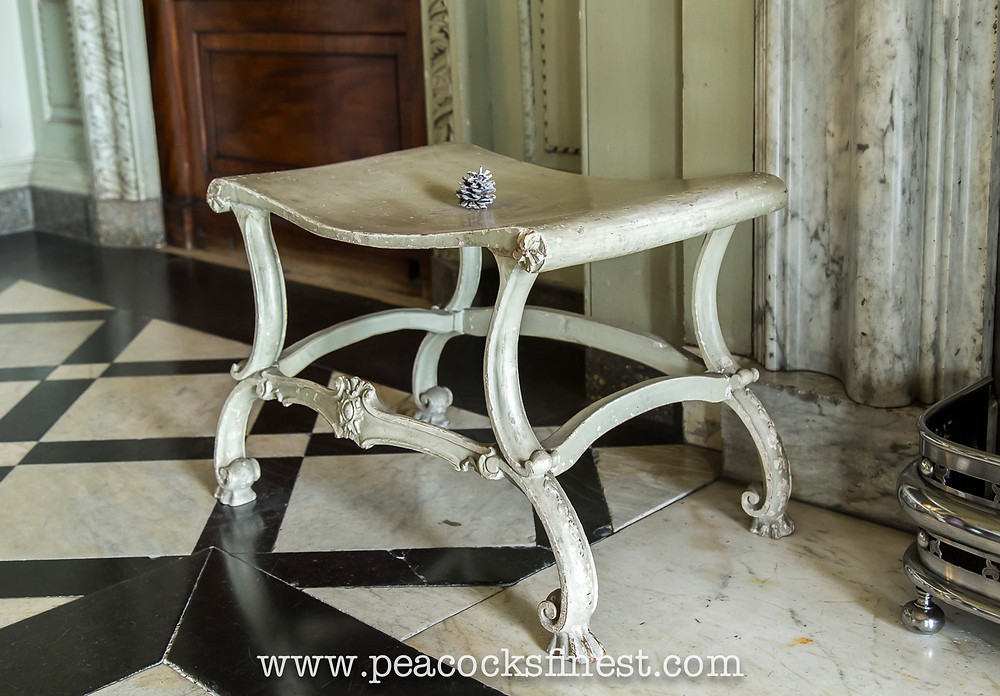A fine painted hall stool, one of a set of four, possibly by Chippendale, at Petworth House.
