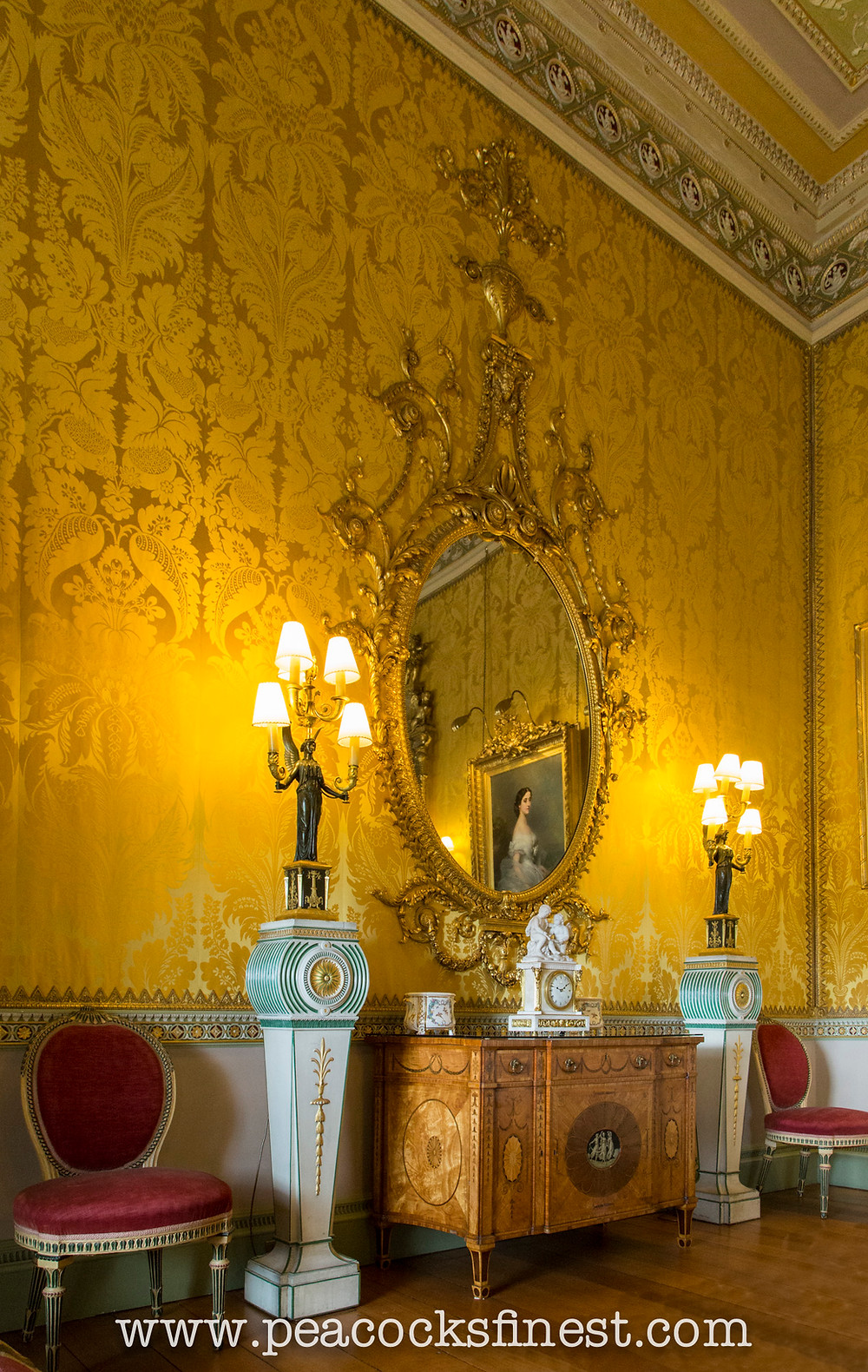Harewood House, The Yellow Drawing Room. A splendid collection of Chippendale's furniture: an ornate mirror, one of a pair, above the magnificent satinwood and marquetry commode, from the State Bedroom suite, a pair of torcheres in the neoclassical taste, and a pair of painted side chairs