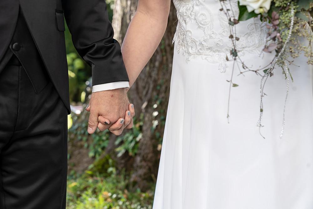 Brautpaar hält sich an Händen
