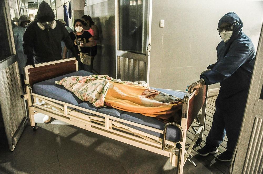 Cuerpo de víctima de la pandemia es llevado por integrantes del equipo humanitario que armarán el féretro. Créditos: Hildebrandt en sus trece/ Hugo Alejos.