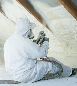 spray polyurethane foam for roof - technician spraying foam insulation using plural component gun fo