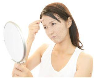 毛穴に角栓が詰まったポツポツ顔を鏡で見て悩む女性