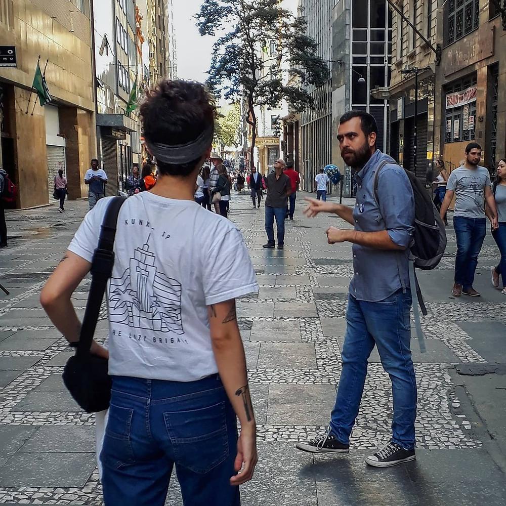 Duas pessoas, uma turista de costas e outra conversando