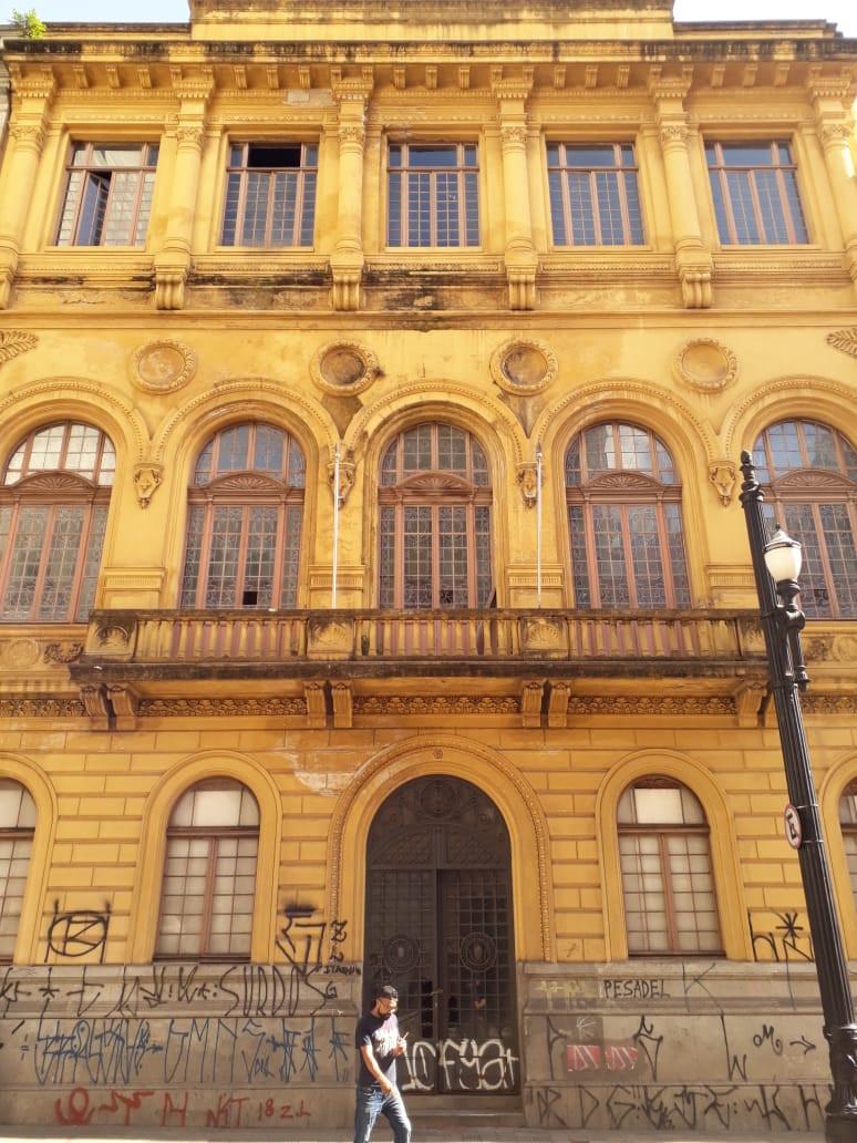 Big Classic Building, windows, doors and a person walking