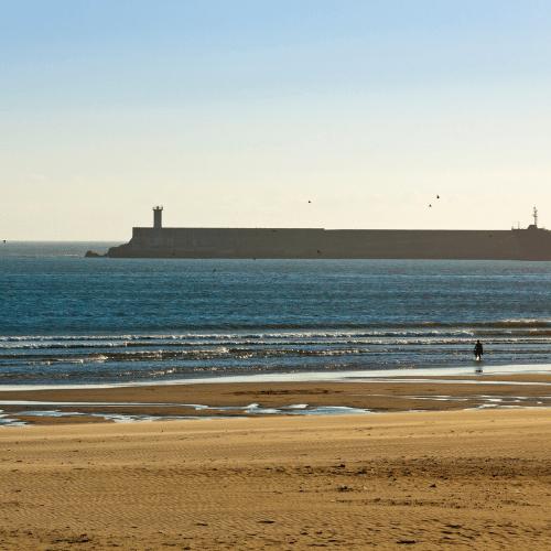Areal e água da praia ao fim de tarde