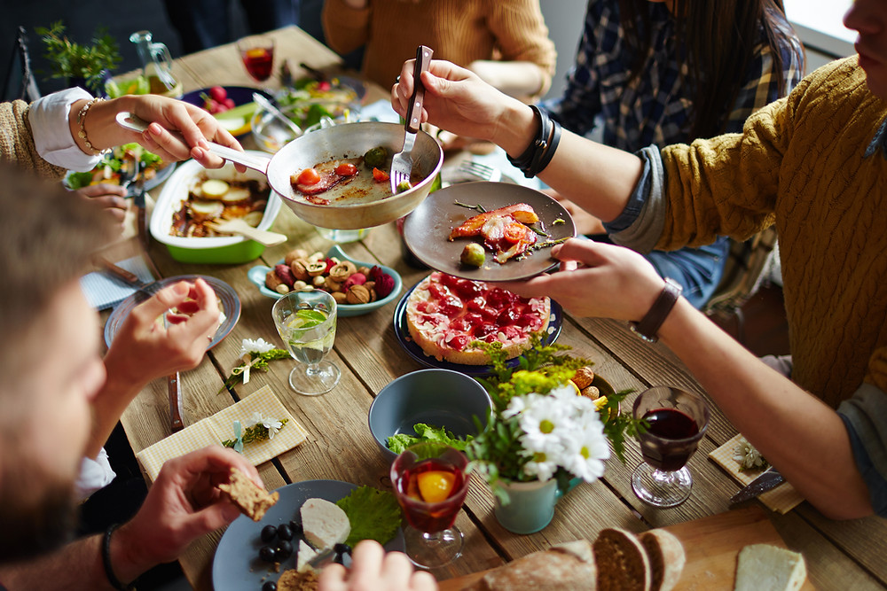 Group of adults sharing delicious food at wood table