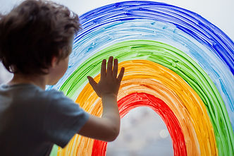 Chase the rainbow. child at home draws a rainbow on the window. Autism Awareness Day, 2 Ap