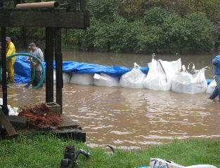 A sandbag dike is constructed at the Syltie Residence so water can be pumped from the house.